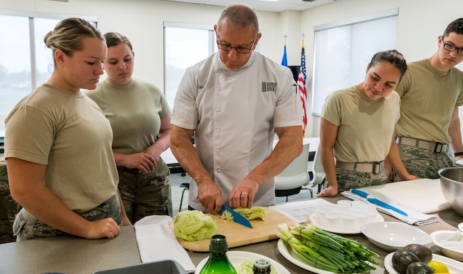 Chef Robert Irvine (center), demonstrates how to shred iceberg lettuce to Dorm to Gourm students, Aug. 27, 2019, at Dover Air Force Base, Del. Irvine taught Team Dover members how to make Cuban-Style Stewed Chicken Ropa Vieja Street Tacos. (U.S. Air Force photo by Roland Balik)