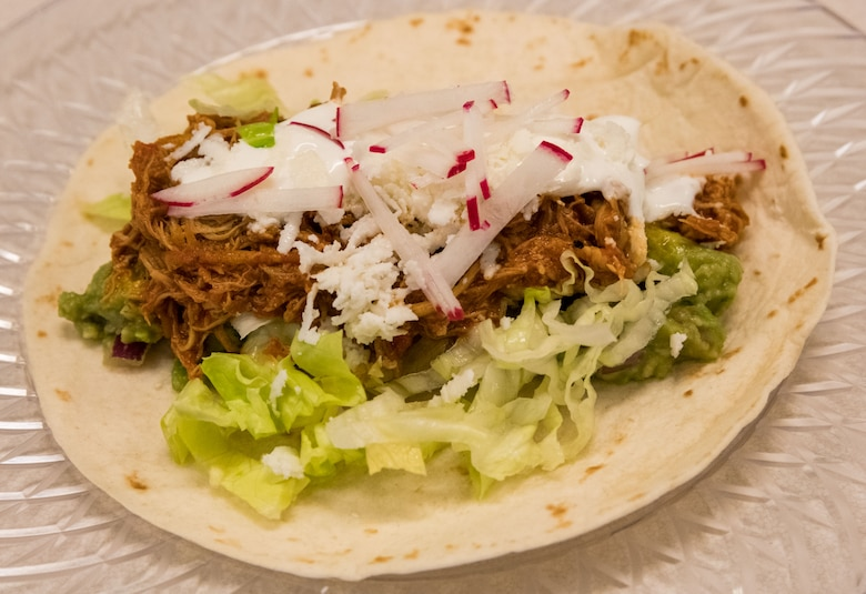 A Cuban-Style Stewed Chicken Ropa Vieja Street Taco made by chef Robert Irvine, sits on a plate during Dorm to Gourm, Aug. 27, 2019, at Dover Air Force Base, Del. The taco consisted of Cuban-style stewed chicken, lime crema fresca, guacamole, queso fresco, shredded iceberg lettuce and breakfast radish on a white corn tortilla. (U.S. Air Force photo by Roland Balik)