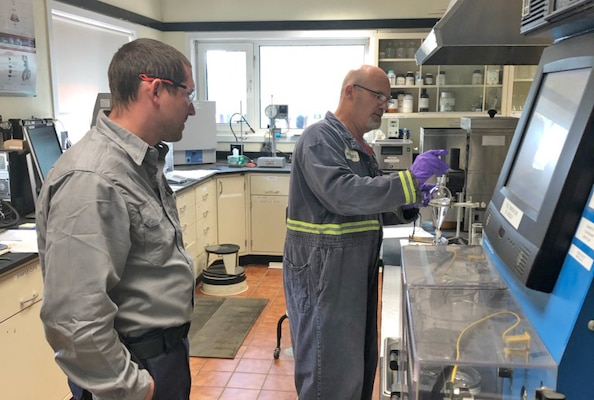 two men in a fuel lab conduct a test