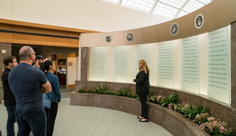 Christin Michaud, Air Force Mortuary Operations Affairs public affairs officer, briefs chef Robert Irvine and his wife, Gail Kim, about the AFMAO memorial wall, Aug. 27, 2019, at Dover Air Force Base, Del. The Memorial Wall represents many of the fallen service members and civilians throughout the years of the mortuary's history. (U.S. Air Force photo by Roland Balik)