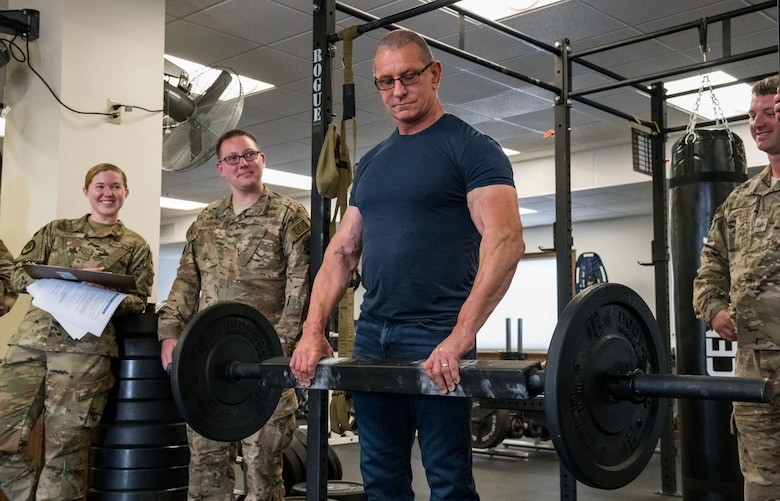 Chef Robert Irvine grasps a 65-pound bar to test his grip endurance during a tour of the 436th Civil Engineer Squadron explosive ordnance disposal flight, Aug. 27, 2019, on Dover Air Force Base, Del. Senior Airman Rachel Zirkle, EOD journeyman; Staff Sgt. Luke Herdade and Tech. Sgt. Carl Dill, both EOD craftsmen, watch Irvine perform the mandatory test for all EOD personnel. (U.S. Air Force photo by Roland Balik)