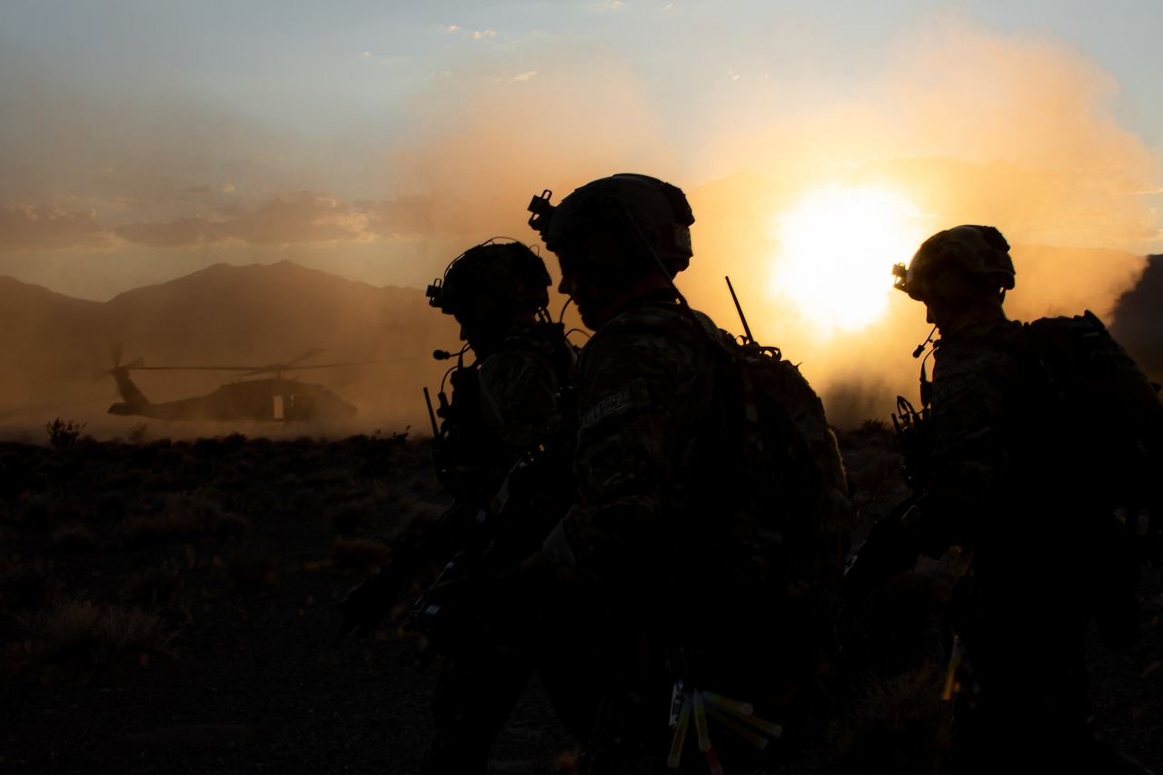 Three service members are silhouetted against the sun with a helicopter in the background.