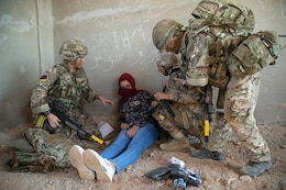 Service members from the Jordan Armed Forces, Mohamed Bin Zayed Brigade/Quick Reaction Force Female Engagement Team and 3 Parachute Regiment, 3rd Battalion provide medical aid to a notional female casualty during a coalition situational training exercise lane during Exercise Eager Lion 19, near Amman, Jordan on Sept. 3, 2019. The JAF FET is comprised of all female soldiers, as a way for the JAF to engage with women in situations in a way that also respects cultural norms.