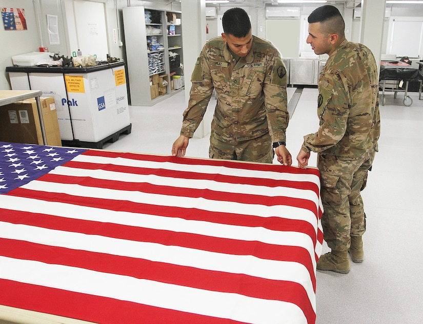 Pfc Edgar Ruiz and Pfc Nahir Gonzalez, 311th Quartermaster Company, inspect an American flag for any flaws at Kuwait City, Kuwait, Aug. 27, 2019.