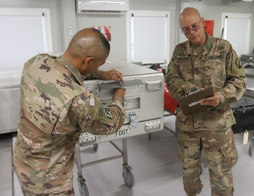 Staff Sgt. David Rodriguez and Sgt 1st Class Alejandro Villarreal, 311th Quartermaster Company,  preform the final inspections and checks on a shipping case in Kuwait City, Kuwait, Aug. 27, 2019.