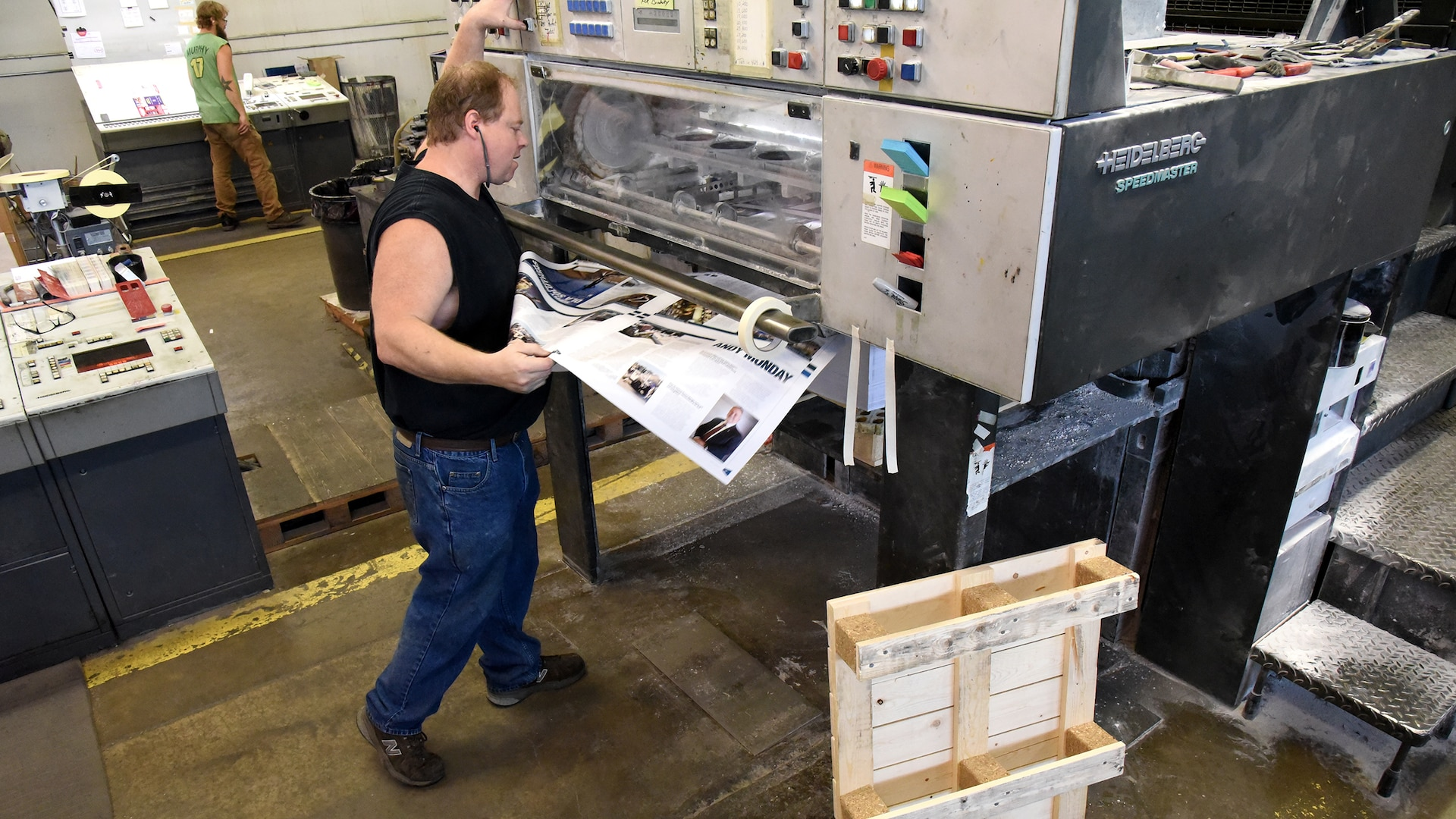 Press Operator Everett E. (Skip) Craig Jr. of KB Offset Printing Inc., in State College, Pennsylvania, pulls a page off the press to randomly check print quality of DLA's Loglines magazine Aug. 26. Photo by Phil Prater