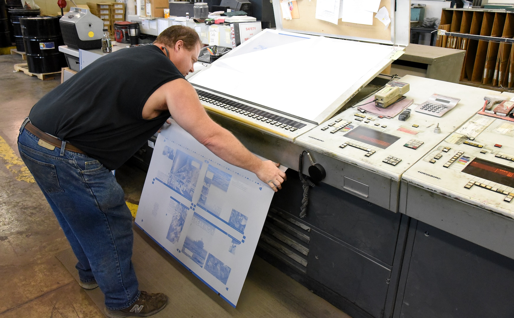 Everett E. (Skip) Craig Jr., press operator at KB Offset Printing Inc. in State College, Pennsylvania, preps a printing plate by crimping its ends to conform to the printing press Aug. 26 for the last issue of DLA's Loglines magazine. Photo by Phil Prater