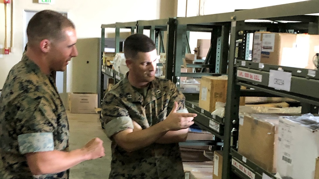 Marine Corps Capt Sean Crilley, aviation readiness officer in charge of the 1st Marine Aircraft Wing's Aviation Logistics Department in Okinawa, Japan, discusses consumable material increases and warehouse management in April with Marine Corps Warrant Officer Richard Hammac, warehouse management division officer in charge of Marine Aviation Logistics Squadron 36's Aviation Supply Department. Photo by Marine Corps Sgt. Youssouf Cherif