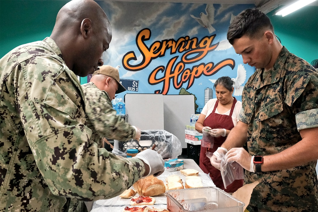 Service members prepare meals at a table.