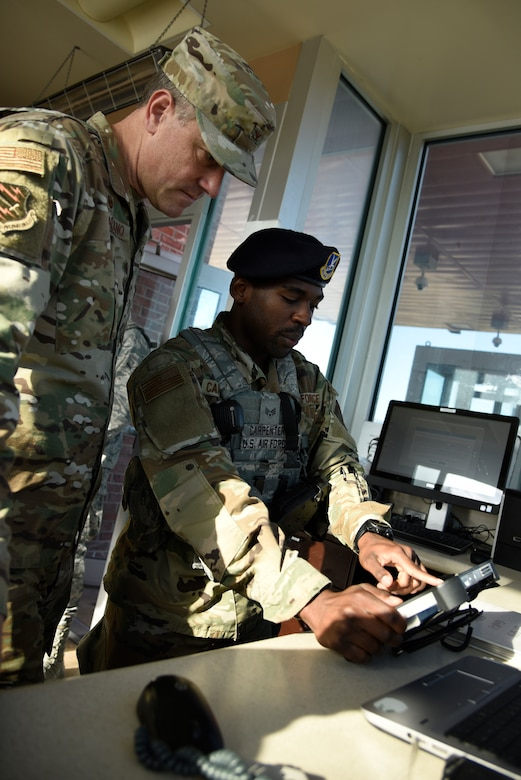 Senior Airman Ricky Carpenter, right, 21st Security Forces Squadron entry controller, explains how the Defense Biometric Identification System computer works to Col. Thomas Falzarano, 21st Space Wing commander, Aug. 16, 2019 at Peterson Air Force Base, Colorado. Carpenter was coined by Falzarano because he recognized him as the incoming commander before his change of command. (U.S. Air Force photo by Staff Sgt. Alexandra M. Longfellow)
