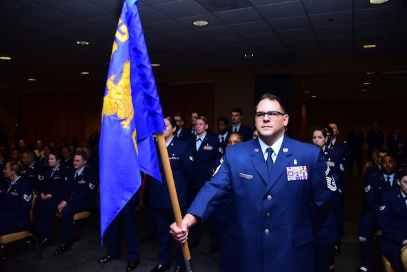 a photo of an airman holding the medical group guidon for a ceremony