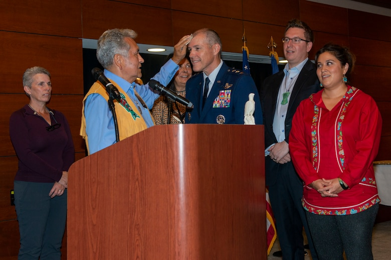 Ed Thomas, Sealaska Board of Directors member, presents a Tlingit name to U.S. Air Force Lt. Gen. Thomas Bussiere, commander, Alaskan North American Aerospace Defense Command Region, North American Aerospace Defense Command; commander, Alaskan Command, U.S. Northern Command; and commander, 11th Air Force, Pacific Air Forces, during an Alaska Native naming ceremony on Joint Base Elmendorf-Richardson, Alaska, Aug. 28, 2019. The AFN hosted the event honoring Bussiere for his service and his active engagement with the Alaska Native community during his tenure in Alaska. The naming ceremony is based on the traditional belief that a person's name is the type of soul they possess. The ceremony showcased the bond between the Alaska Native community and the military in Alaska.