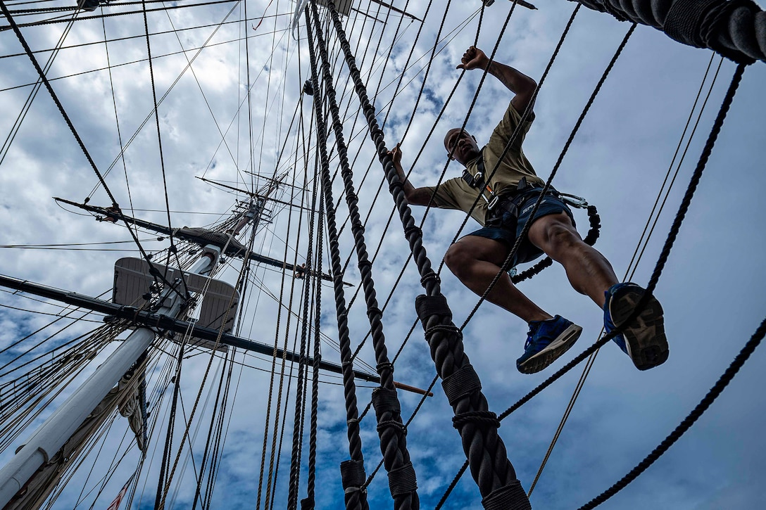 A sailor climbs a mast of a ship.