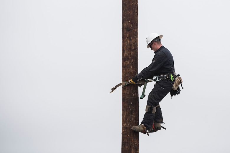 Staff Sgt. Lonnie Elliott, 30th Civil Engineer Squadron electrician, climbs a power pole during pole-top rescue training Aug. 23, 2019, at Vandenberg Air Force Base, Calif. During the training, each service member had four minutes to climb a power pole, retrieve a dummy, and hoist the dummy safely to the ground. The Airmen utilize this training to learn the techniques necessary to perform emergency pole-top rescues. (U.S. Air Force photo by Hanah Abercrombie)