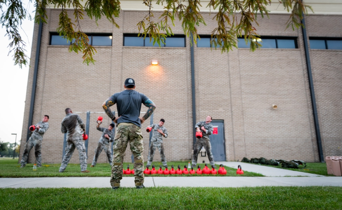 A 352nd Special Warfare Squadron training instructor looks on as Airmen from the 352nd SWTS participate in a memorial physical training session outside of Matero Hall on Keesler Air Force Base, Mississippi, Aug. 9, 2019. The PT event was in memory of U.S. Air Force Staff Sgt. Andrew Harvell, combat controller, who was killed in action on Aug. 6, 2011. Special Warfare trainees also attend courses in the 334th and 335th Training Squadrons. (U.S. Air Force photo by Sarah Loicano)