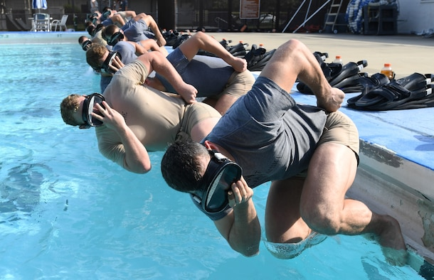 Special Warfare trainees from the 352nd Special Warfare Training Squadron participate in a memorial physical training session at the Triangle Pool on Keesler Air Force Base, Mississippi, Aug. 9, 2019. The PT event was in memory of U.S. Air Force Staff Sgt. Andrew Harvell, combat controller, who was killed in action on Aug. 6, 2011. Special Warfare trainees also attend courses in the 334th and 335th Training Squadrons. (U.S. Air Force photo by Kemberly Groue)