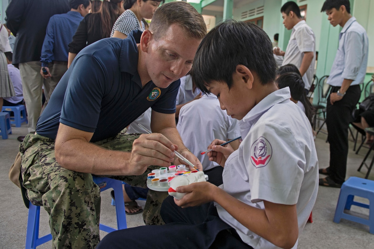 Navy lieutenant helps a child using watercolors to paint a small statue.
