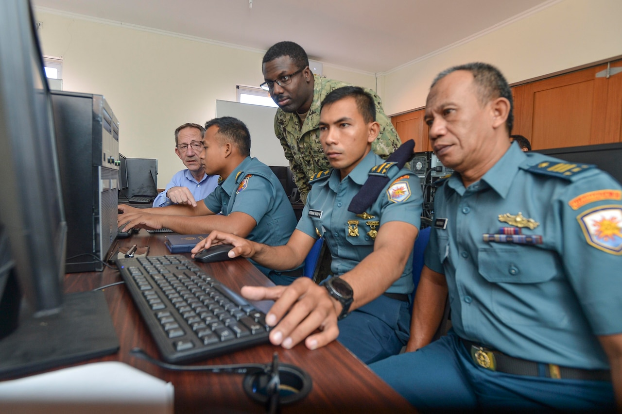 U.S. Navy sailor looks at a computer monitor with sailors from the Indonesian navy.