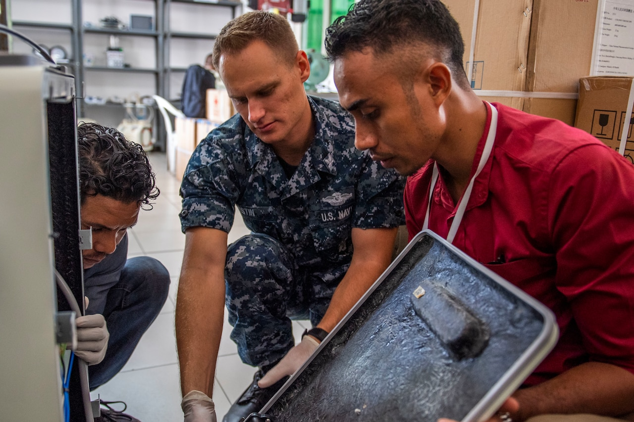 U.S. sailor in uniform and two civilians remove a large panel from a piece of medical equipment.