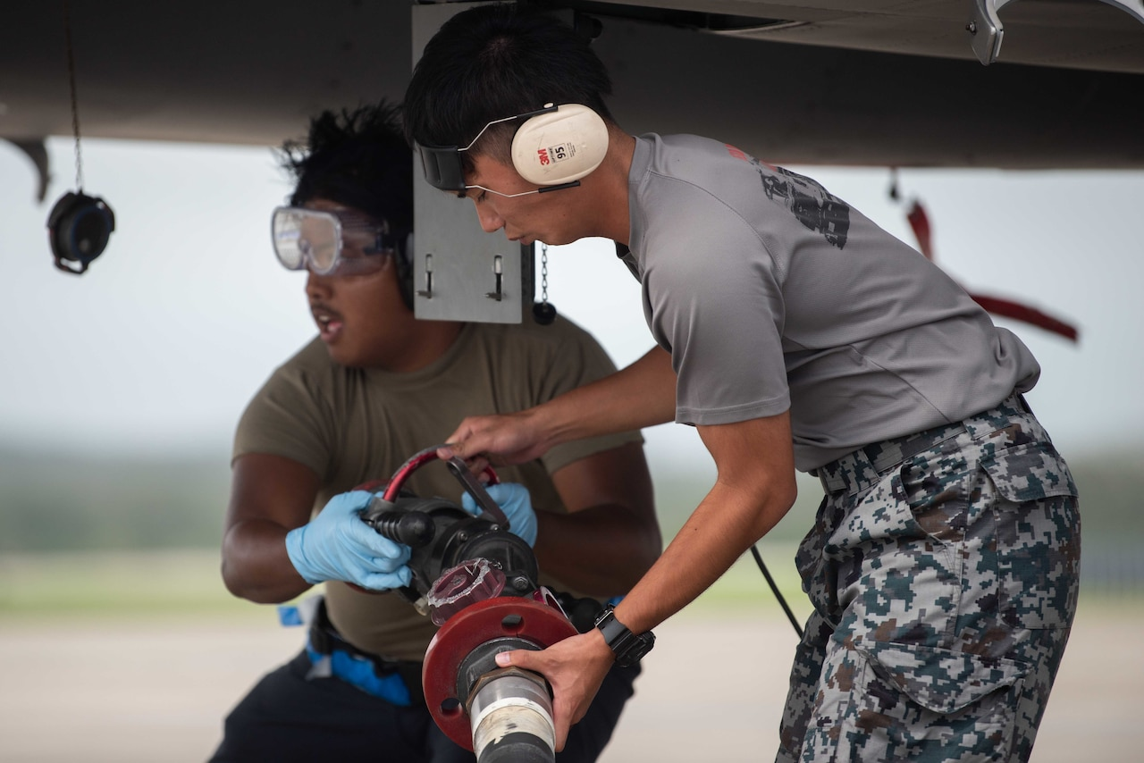 U.S. and Japanese service members work under an aircraft wing.