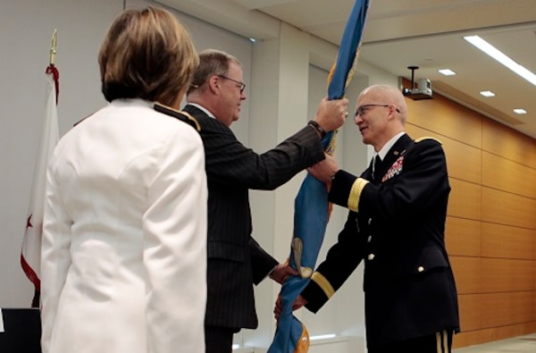 Assistant Secretary of Defense for Health Affairs Tom McCaffery (center), passes the colors to the new DHA director, Army Lt. Gen. Ronald Place (right), as Navy Vice Adm. Raquel Bono, the outgoing director of the Defense Health Agency, watches.
