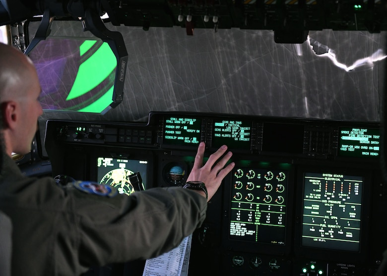A man presses buttons on dashboard in the cockpit of a plane