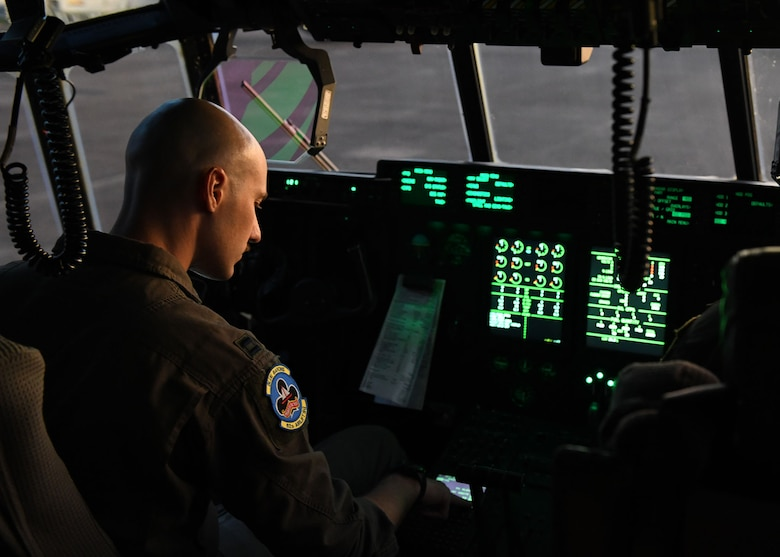 A man looks at a piece of paper that is clipped on the dashboard inside the cockpit of an airplane
