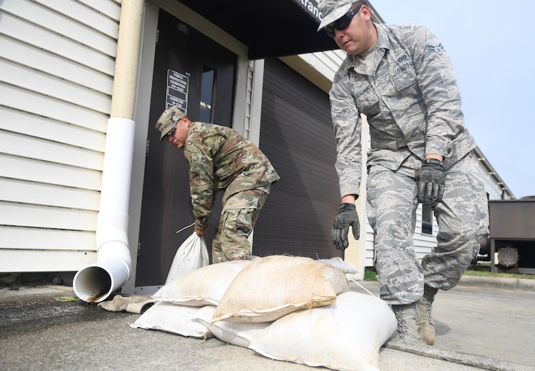 Seymour Johnson Air Force Base, N.C. — SSgt Manuel Acuna and Airman 1st Class Torre Ruano, 4th Civil Engineer Squadron pavement and production specialists, stack sand bags Sept. 4, 2019, at Seymour Johnson Air Force Base, North Carolina in front of th 4th CE headquarters building. The 4th CES, to include equipment operators, electricians, plumbers, structural craftsman, heating, ventilation and air conditioning, and production technicians, are providing 24-hour response and recovery operations during and following Hurricane Dorian. (U.S. Air Force photo by Staff Sgt. Michael Charles)