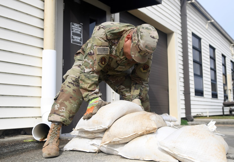 Seymour Johnson Air Force Base, N.C. — SSgt Manuel Acuna, 4th Civil Engineer Squadron pavement and production specialist, stack sand bags in front of a building on the installation Sept. 4, 2019, at Seymour Johnson Air Force Base, North Carolina. The 4th CES, to include equipment operators, electricians, plumbers, structural craftsman, heating, ventilation and air conditioning, and production technicians, are providing 24-hour response and recovery operations during and following Hurricane Dorian. (U.S. Air Force photo by Staff Sgt. Michael Charles)
