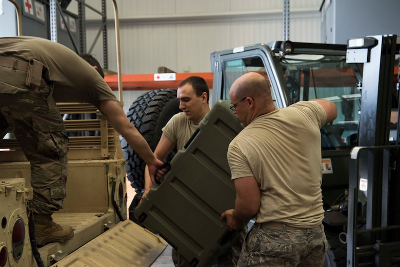 U.S. Air Force Airman 1st Class Benjamin Lippold, a biomedical equipment technician, and Master Sgt. Ursus Vargas, a medical material section chief, both with the 6th Medical Support Squadron (MDSS), load cargo into a Humvee at MacDill Air Force Base, Fla., Sept. 4, 2019. The 6th MDSS was tasked by Air Mobility Command's chief of Readiness to prepare equipment for use in hurricane relief. (U.S. Air Force Photo by Senior Airman Frank Rohrig)