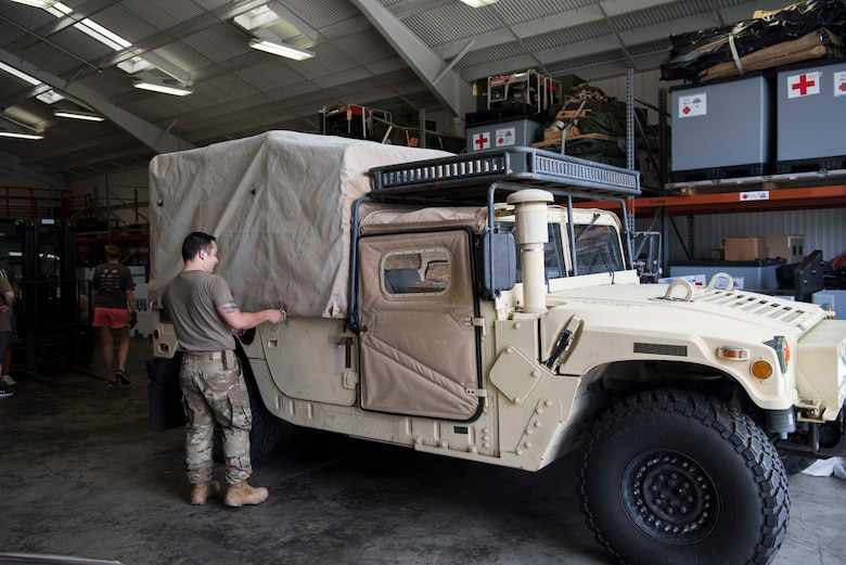 U.S. Air Force Staff Sgt. Dustin Johnson, a 6th Medical Support Squadron (MDSS) biomedical equipment technician, secures the cover of a Humvee at MacDill Air Force Base Fla., Sept. 4, 2019. Air Mobility Command's Chief of Readiness asked the 6th Medical Support Squadron (MDSS) to prepare equipment for use in hurricane relief. (U.S. Air Force Photo by Senior Airman Frank Rohrig)