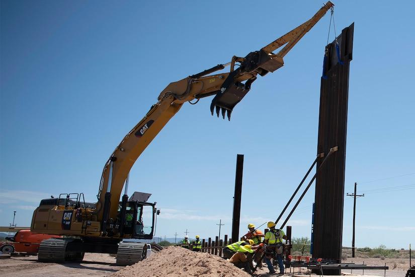 Crew members install bollard wall.