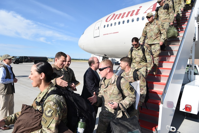 Airmen walk down stairs of aircraft and greet senior leaders