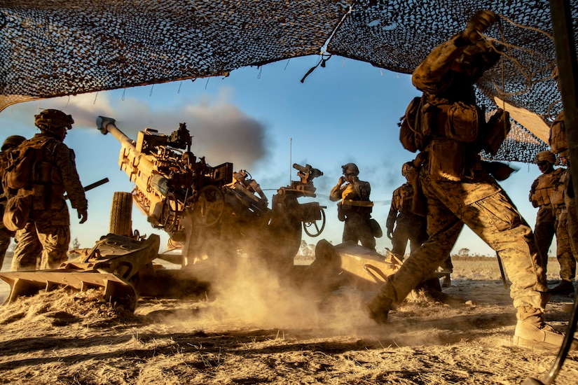 A group of Marines fire a howitzer.