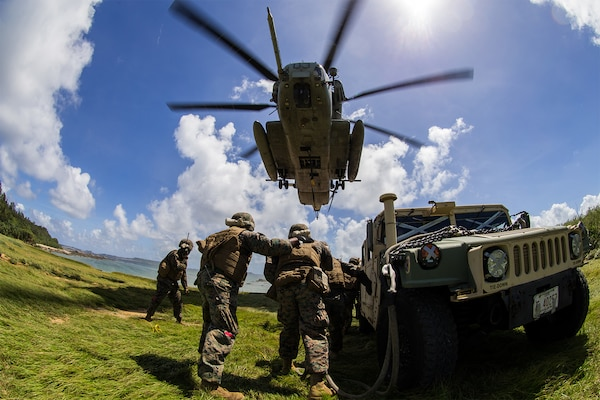 Marines stand by a vehicle under a helicopter.