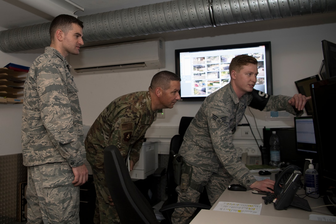 U.S. Air Force Chief Master Sgt. Randy Kwiatkowski, Third Air Force command chief, center, talks to 569th United States Force Police Squadron, 1st Lieutenant Stephen Cromp, operations officer, left, and Senior Airman Kaleb Cherry, alarm monitor, right, on Kapaun Air Station, Germany, July 26, 2019. Kwiatkowski received a day-long tour of operations to better familiarize himself with the mission set of the Kaiserslautern Military Community. (U.S. Air Force photo by Staff Sgt. Nesha Humes Stanton)