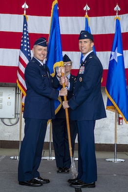 U.S. Air Force Maj. Gen. John Wood, 3rd Air Force commander, passes the 52nd Fighter Wing guidon to Col. David Epperson, incoming 52nd Fighter Wing commander, during the wing change of command ceremony in Hangar 1 at Spangdahlem Air Base, Germany, Sept. 04, 2019. Epperson is now the commander of five groups, 24 squadrons, and 11 geographically separated units spread across five countries with approximately 5,000 dedicated military and civilian personnel. (U.S. Air Force photo by Airman 1st Class Branden Rae)