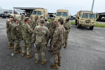 U.S. Army Staff Sgt. Draper Daniels (front-center of group), B Company, 1-118th Infantry Battalion from North Charleston, South Carolina, briefs the crews of four South Carolina National Guard Light Medium Tactical Vehicles (LMTV) assigned to the 1-118th Infantry Battalion of their assignments to local fire departments throughout the city of Charleston, South Carolina in preparation to assist local first responders with rescue calls caused by Hurricane Dorian, Sept. 4, 2019.