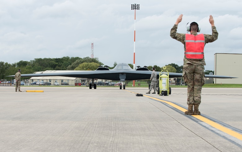 An Airman assigned to the 509th Bomb Wing marshals in Major General James Dawkins Jr., Eighth Air Force commander, as he taxis in a B-2 Spirit on the flight line of Royal Air Force Base Fairford, England, on August 28, 2019. Dawkins flew the stealth bomber during his visit to engage with members of Whiteman Air Force Base, Missouri, who had deployed to Royal Air Force Fairford as a Bomber Task Force to conduct theater integration and flying training. (U.S. Air Force photo by Staff Sgt. Kayla White)