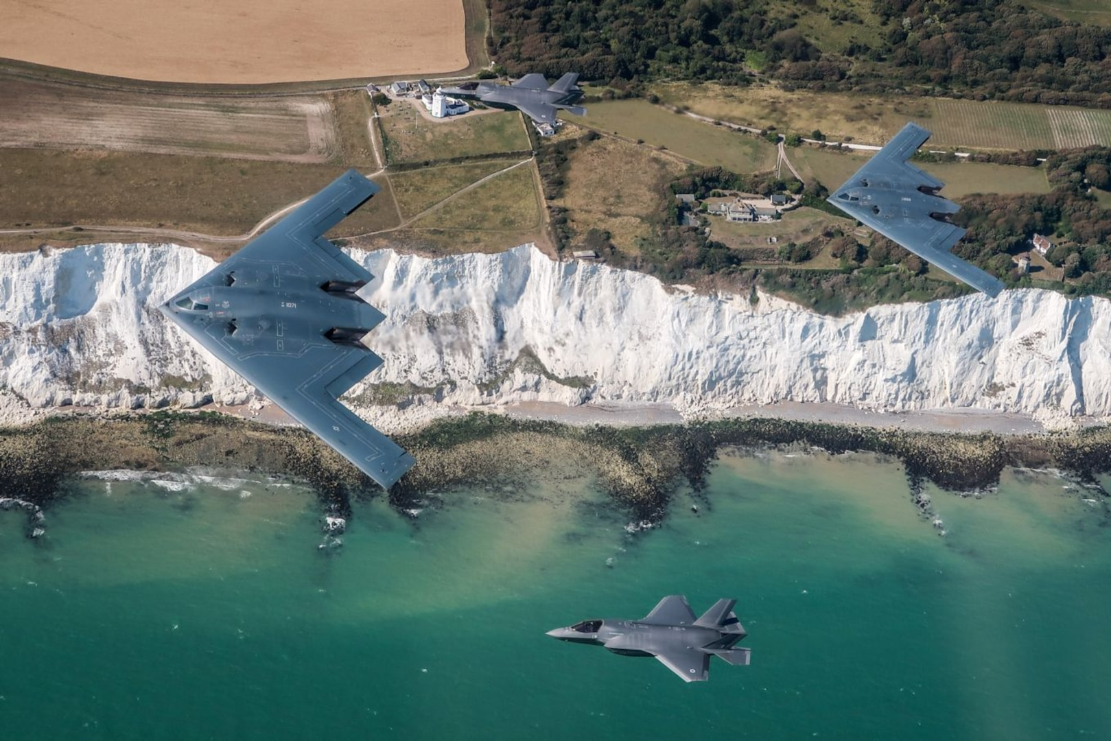 A U.S. Air Force B-2 Spirit, currently deployed to RAF Fairford in Gloucestershire, England, flies above the English countryside near Dover with two RAF F-35 jets, August 30, 2019. This is the first time UK F-35 Lightening jets have conducted training with the U.S. B-2 stealth bomber. (Courtesy Photo)