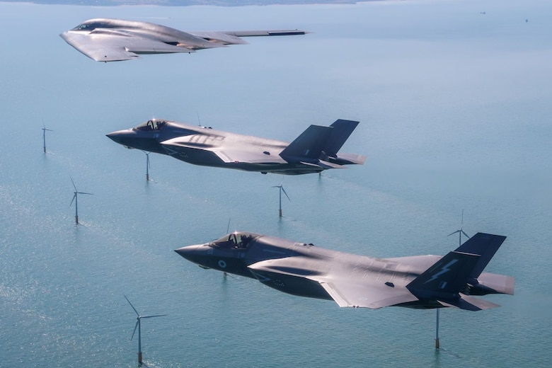 A U.S. Air Force B-2 Spirit, currently deployed to RAF Fairford in Gloucestershire, England, flies above the English countryside near Dover with two RAF F-35 jets. This is the first time UK F-35s have conducted training with the stealth bomber.