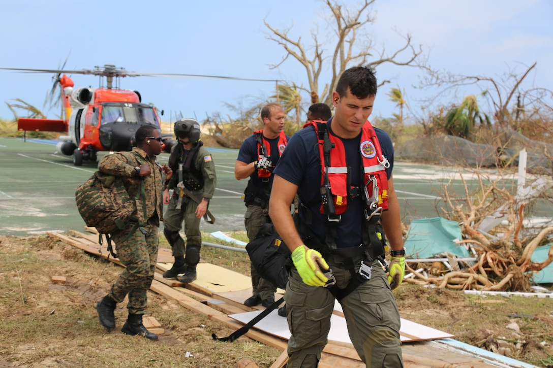 A Coast Guard Air Station Clearwater MH-60 Jayhawk helicopter crew Petty Officer 2nd Class Sam Fuller, Petty Officer 2nd Class Mike Lewis, Petty Officer 2nd Class Jethro Hauser, Ltcdr. Tony Lumpkin and Lt. Travis Rhera in support of search and rescue and humanitarian aid in the Bahamas, Sept. 4, 2019.