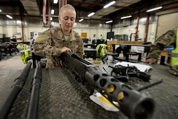 Sgt. Brittany Deturo, weapons quality assurance, 401st Army Field Support Battalion-Kuwait, disassembles a M2 .50-caliber machine gun in the weapons maintenance facility of Army Prepositioned Stocks-5, Aug. 17, Camp Arifjan, Kuwait. Deturo is a member of the 776 Support Maintenance Company of the Tennessee National Guard.