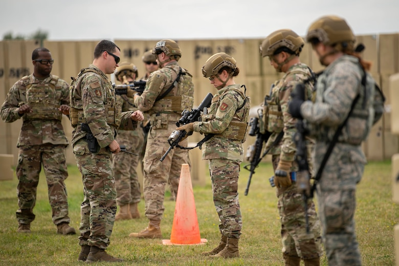Chief Master Sgt. Kathi Glascock, center, 100th Air Refueling Wing command chief, prepares an M4 Carbine for advanced shoot, move and communicate training with Airmen from the 100th Security Forces Squadron at RAF Mildenhall, England, Aug. 30, 2019.  The purpose of the training was for the defenders to demonstrate their advanced combat skills for the commander and command Chief. (U.S. Air Force photo by Senior Airman Luke Milano)