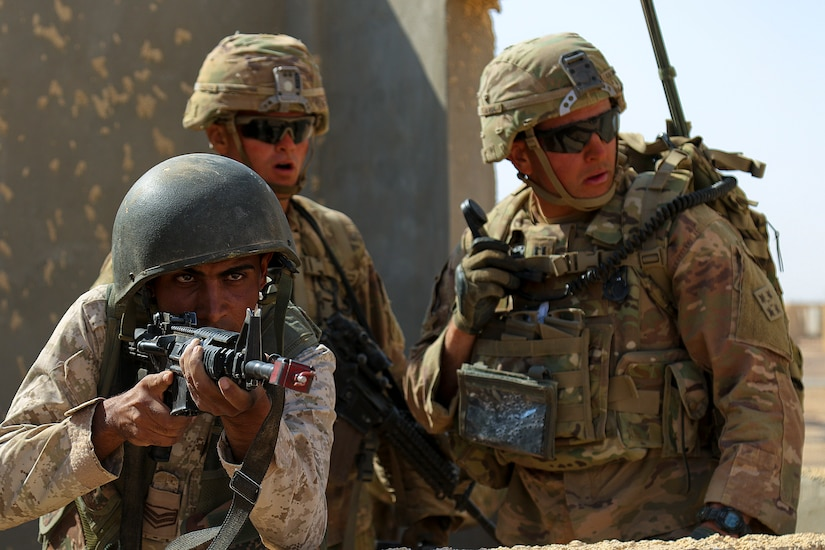 A Royal Jordanian Army Soldier from the 39th Mechanized Infantry Battalion provides security while Soldiers from the U.S. Army's 3rd Armored Brigade Combat Team, 4th Infantry Division, call out enemy objectives during a situational training exercise- part of Eager Lion 2019- at an urban assault training village near Amman, Jordan, Sept. 2, 2019.