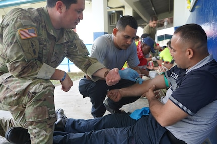 Military personnel practice proper catheter insertion application.
