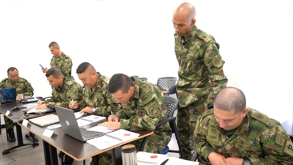 Military personnel sit at desks.