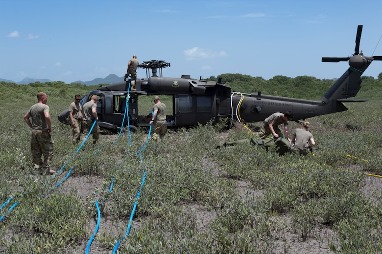 Soldiers from the 1st Battalion 228th Aviation Regiment connect sling cables to a UH-60 Blackhawk for it to be carried from an austere riverbank to Liberia Airport in Costa Rica July 29, 2019. During a mission to support the USNS Comfort, the UH-60 crew performed a precautionary landing in an austere environment in Costa Rica. After inspecting the Blackhawk, the crew determined that aircraft was not safe to fly. Joint service members from Joint Task Force - Bravo worked together, with the assistance of a C-17 Globemaster III from U.S. Transportation Command, to return the broken helicopter back to Soto Cano. (U.S. Air Force photo by Tech. Sgt. Eric Summers Jr.)