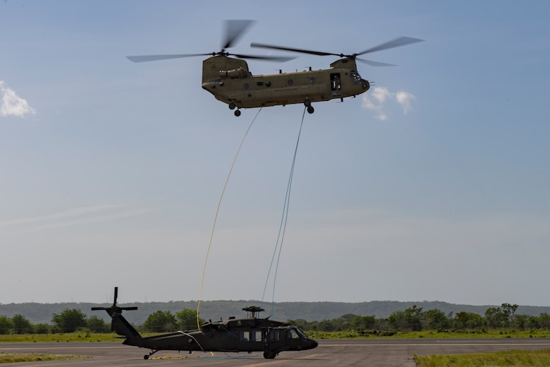 A CH-47 Chinook from the 1st Battalion 228th Aviation Regiment places a broken UH-60 on the flightline on Liberia Airport, Costa Rica, July 29, 2019. During a mission to support the USNS Comfort, the UH-60 crew performed a precautionary landing in an austere environment in Costa Rica. After inspecting the Blackhawk, the crew determined that aircraft was not safe to fly. Joint service members from Joint Task Force - Bravo worked together, with the assistance of a C-17 Globemaster III from U.S. Transportation Command, to return the broken helicopter back to Soto Cano. (U.S. Air Force photo by Tech. Sgt. Eric Summers Jr.)