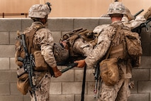 U.S. Marines with 3rd Battalion, 7th Marine Regiment, 1st Marine Division, move a simulated casualty over a wall during counter improvised explosive device training at Marine Corps Air Ground Combat Center, Twentynine Palms, Calif., July 25, 2019. The training was designed to improve the confidence and proficiency in the skill sets Marines and sailors need to operate in an urban environment. (U.S. Marine Corps photo by Lance Cpl. Colton Brownlee)